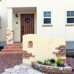 丸い開口が可愛い、塗り壁とスリムレンガで門柱